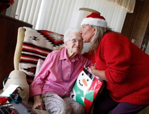 Mark Brown/Staff Marianne Buckmeyer of Home Instead Senior Care gives a kiss and a gift to 103-year-old Martha Dear at her home in Nipomo. Dear was treated to the gift as part of the Santa to a Senior program. 112910